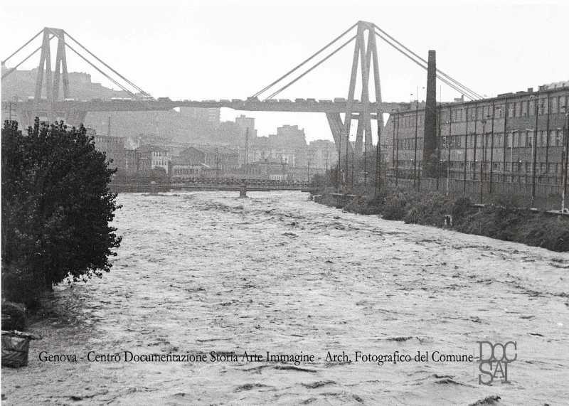 Il 'Morandi' si staglia sullo sfondo del torrente Polcevera in piena durante la grande alluvione del 1970